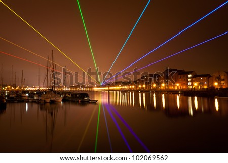 PRESTON, ENGLAND - MARCH 11: Laser light show forming the Global Rainbow by Yves Mattern on March 11, 2012 at Preston Docks. The show is touring the UK in association with the London Olympics. - stock photo