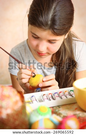 preteen beautiful girl paint boiled eggs for easter holiday party - stock photo