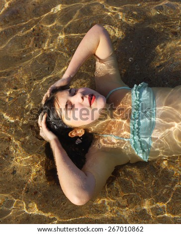 preteen beautiful girl with long dark hair in swimming suit swimming in the red  sea in egypt - stock photo