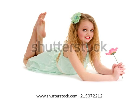 Preteen Blond Dancer Girl Holds a Flower Lying on Tummy on Floor - stock photo