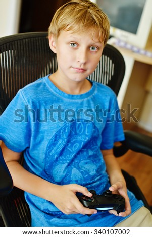 preteen boy at home with video game controller  - stock photo