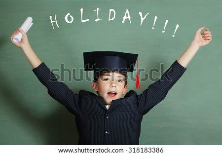 preteen boy in business suit and graduation cap cheer about coming holiday - stock photo