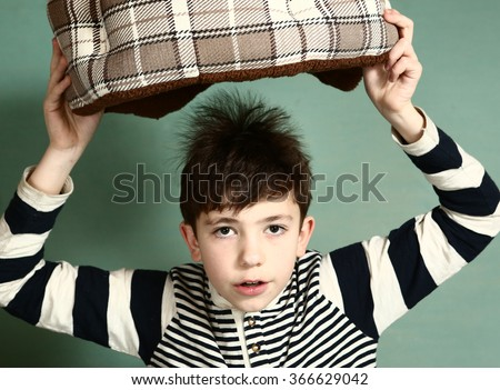 preteen boy show physical experiment produce electricity by rubbing his hair with woolen cloth and make his hair stand on end - stock photo