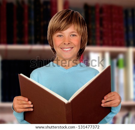 Preteen boy with a big book reading in the library - stock photo