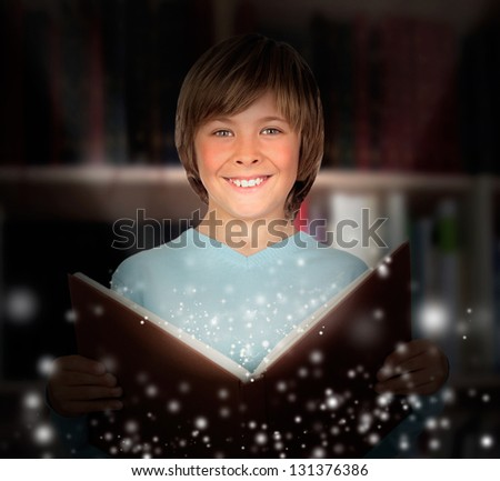 Preteen boy with a lighted book reading in the library - stock photo