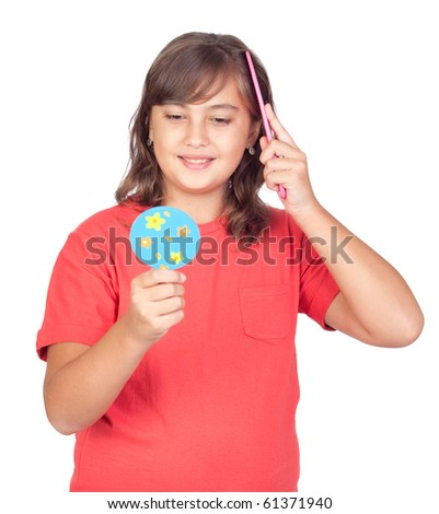 Preteen girl combing with a comb in front of a mirror isolated on white background