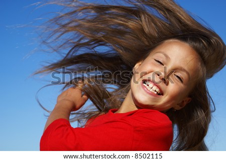Preteen girl flipping hair on blue sky background - stock photo