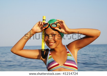 Preteen girl in diving outfit enjoying sun-bath on sea beach - stock photo