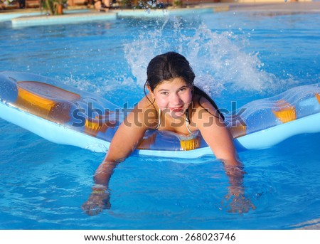 preteen girl in swimming suit with inflatable matrass in the open air swimming pool in the beach hotel resort - stock photo