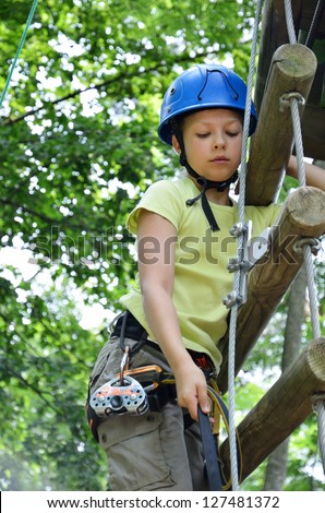 Preteen girl is climbing on the rope ladder at the ropes course. She is photographed in the green forest.