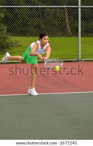 Preteen girl playing tennis - stock photo