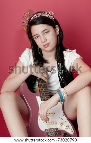 Preteen girl sitting on ground holding electric guitar