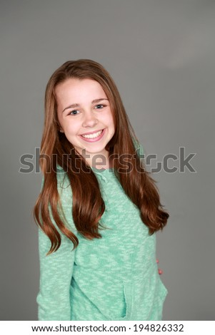 preteen girl smiling and looking at camera - stock photo
