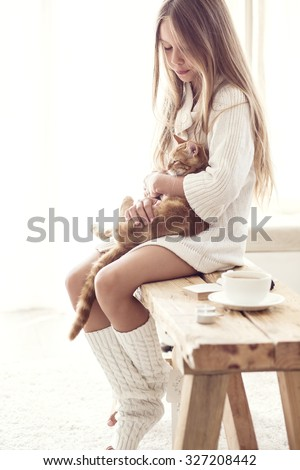 Preteen girl wearing warm knitted clothing is sitting on rustic bench with her cat in white living room. Winter weekend. - stock photo