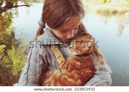 Preteen girl with red cat in her arms. Photo toned style Instagram filters. - stock photo