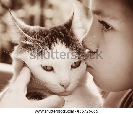 preteen handsome boy and cat close up monochrome sepia black and white bw photo on green garden background - stock photo