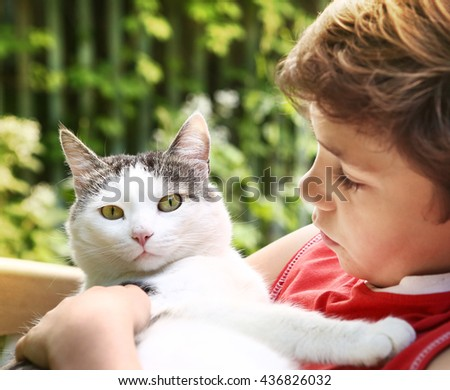 preteen handsome boy and cat close up photo on green garden background - stock photo