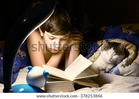 preteen handsome boy evening read book with cat in the bed before sleeping - stock photo