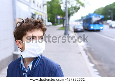 preteen handsome boy in protective mask on the urban background