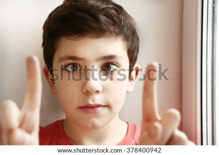 preteen handsome boy play squinting trick with his eyes and fingers close-up portrait - stock photo