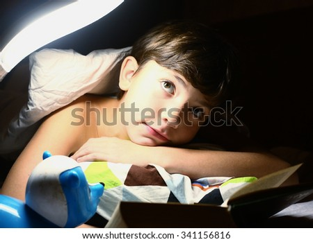preteen handsome boy read book in bed with night lamp - stock photo