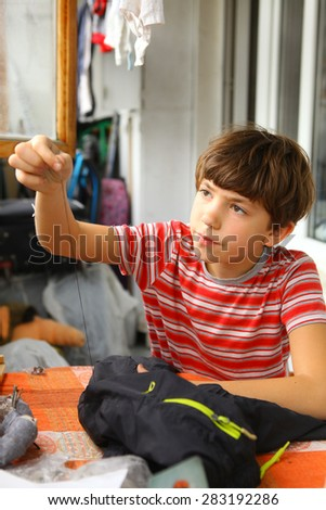preteen handsome boy sew hole in the torn trousers - stock photo