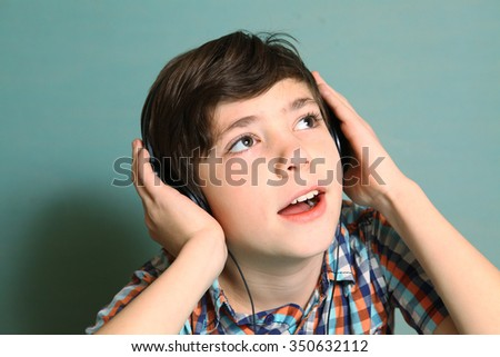 preteen handsome boy with headphones listen to popular mp3 music on computer close up expression portrait isolated on blue - stock photo