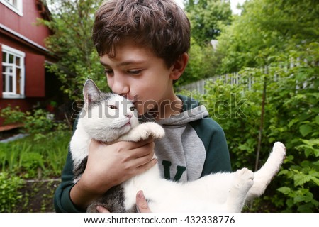 preteen handsome boy with siberian tom cat close up country summer portrait with cottage house on the background - stock photo