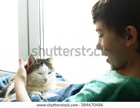 preteen handsome boy with tom mail cat lay in bed close up photo - stock photo