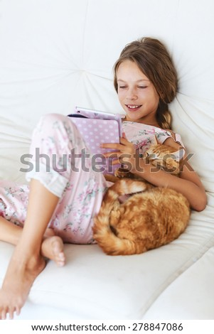 Preteen school girl of 8-9 years old playing on ipad tablet pc and hugging her cat resting on a sofa at home - stock photo