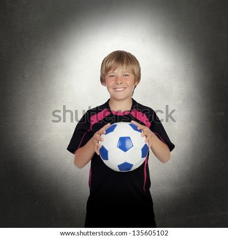 Preteen with a uniform for play soccer with a gray background - stock photo