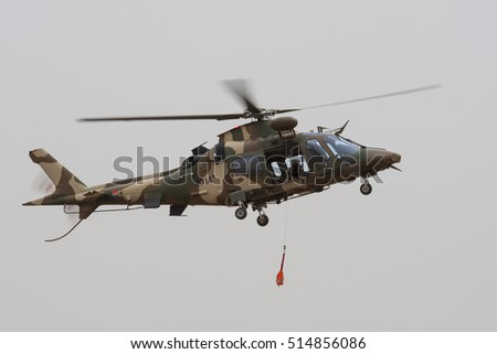 PRETORIA, SOUTH AFRICA-SEPTEMBER 17 2016: An Agusta A109 light utility helicopter in camouflage colors lowers a rescue harness during the African Air Defense show at AFB Waterkloof