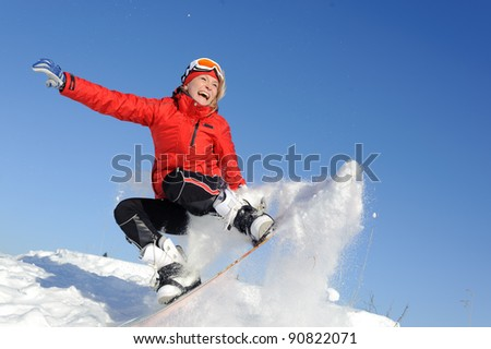 Pretty active young woman in red clothing on snowboard - stock photo