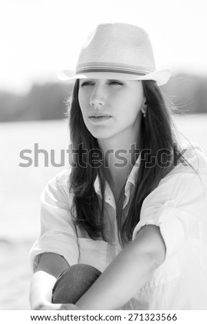 Pretty adult girl in white hat at summer beach. Black and white portrait of young caucasian woman near water - stock photo