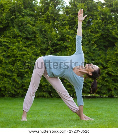 pretty adult woman doing yoga on green grass in summer park - stock photo