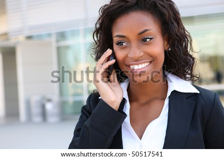 Pretty african american business woman talking on her mobile phone at office building - stock photo