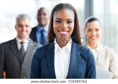 pretty african american businesswoman standing in front of co-workers - stock photo
