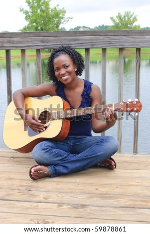 pretty african-american with guitar sitting on dock - stock photo