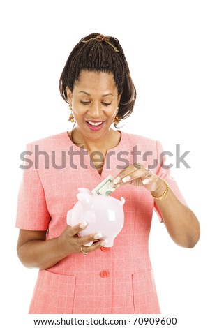 Pretty african-american woman saving money in her piggy bank.  Isolated on white.