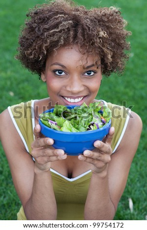 pretty African American woman with a healthy salad in a park - stock photo