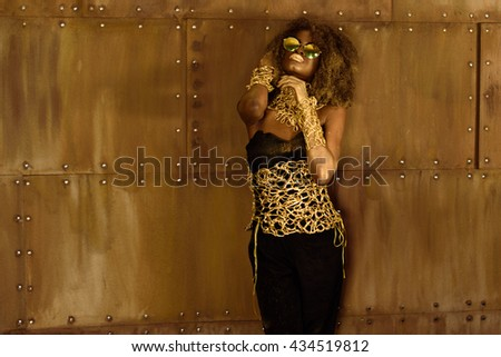 Pretty African American woman with golden makeup and sunglasses holding hands near face in front of bronze wall - stock photo