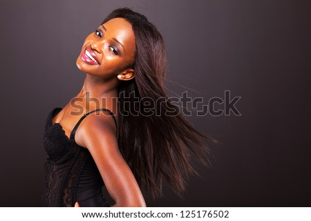 pretty african american woman with long hair on black background - stock photo