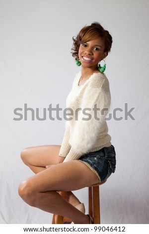 Pretty African American young woman in shorts and a white shirt sitting on a stool with a happy, friendly smile - stock photo