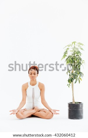 Pretty african american young woman meditating and practicing yoga near small tree in pot over white background - stock photo