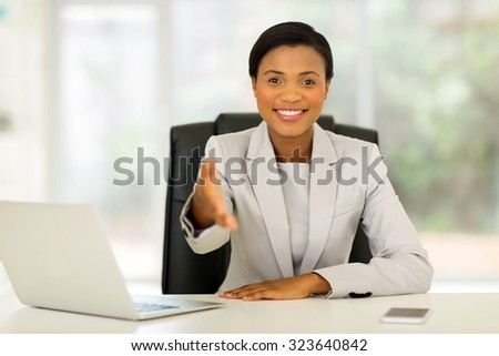 pretty african businesswoman offering handshake in office - stock photo