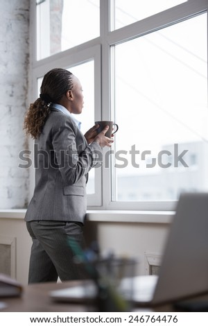 Pretty african businesswoman standing near window and drinking coffee or tea while resting and thinking about something - stock photo