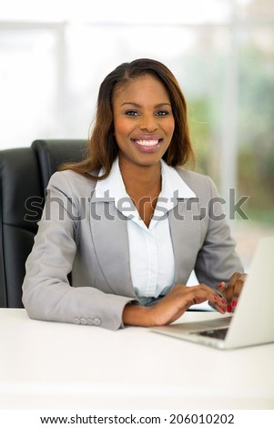 pretty african businesswoman using computer in office - stock photo
