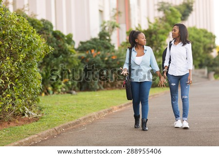 pretty african college students walking together on campus - stock photo