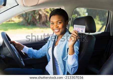 pretty african woman in a car showing her driver's license - stock photo