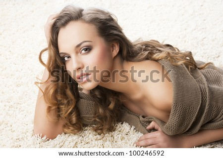 pretty and attractive young brunette in a warm brown sweater laying down on a white carpet, she looks in to the lens with sensual expression,  her right hand is near the face and the left hand is on - stock photo